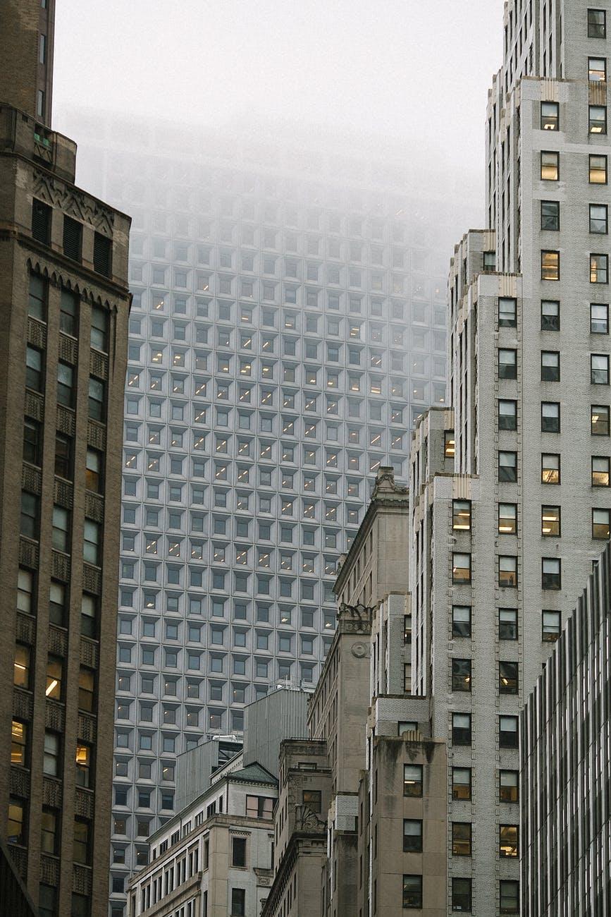 contemporary multistory house facades under foggy sky in city